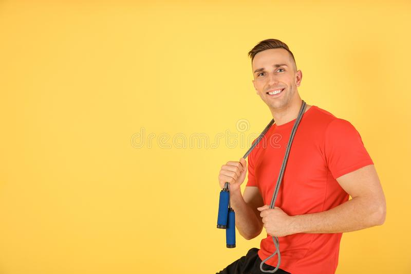 Portrait of young sportive man with jump rope on color background. Space for text stock images