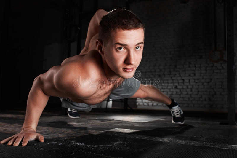 Portrait of a young sportsman doing push ups exercise with one hand against brick wall in fitness gym. royalty free stock image
