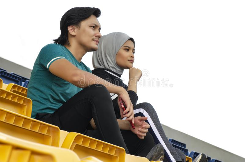 Sportsman and woman sitting and talking each other stock photography