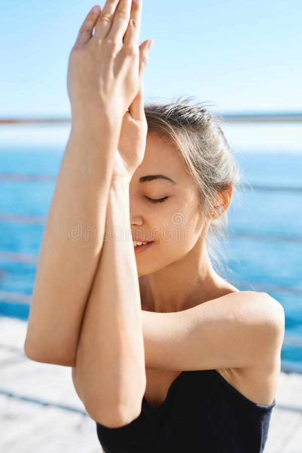 Portrait of a young sporty attractive woman practicing yoga, doing Garudasana arms exercise at the beach with sea stock images