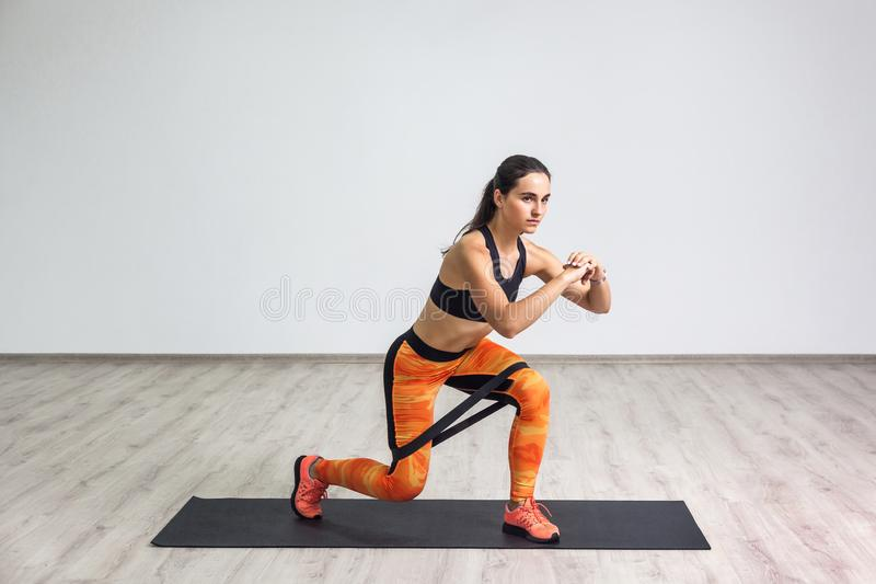Portrait of young sporty healthy attractive woman in black top and orange leggings doing lunge with elastic latex resistance band. Isolated, white wall, indoor royalty free stock photography