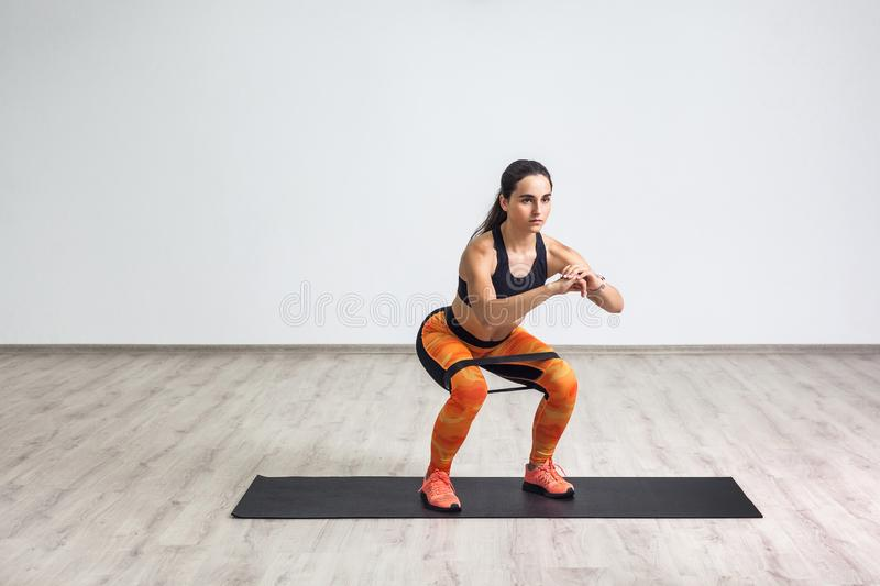 Portrait of young sporty healthy beautiful woman in black top and orange leggings doing squatting with elastic resistance band. Isolated, white wall, indoor royalty free stock image