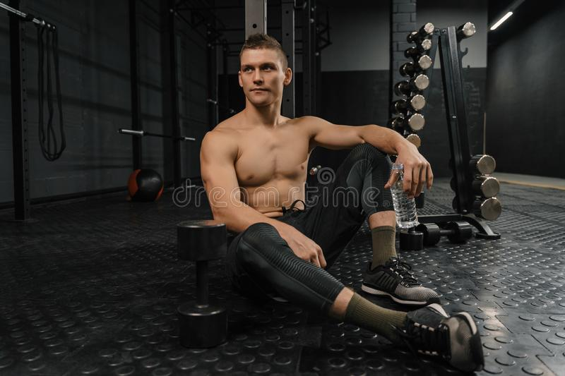 Portrait of young sporty man with bottle rest in gym after workout royalty free stock photos
