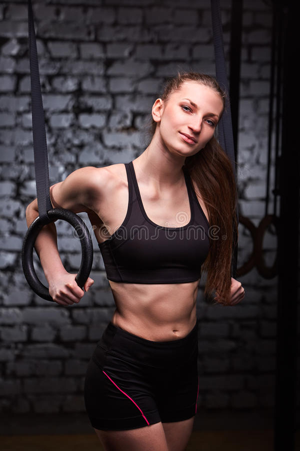 Portrait of a young sporty woman in the black sportwear training arms with gymnastics rings against brick wall. stock images