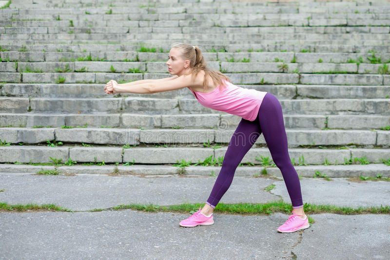 Portrait of young sporty woman in sport dress does stretching exercises outdoor royalty free stock photo