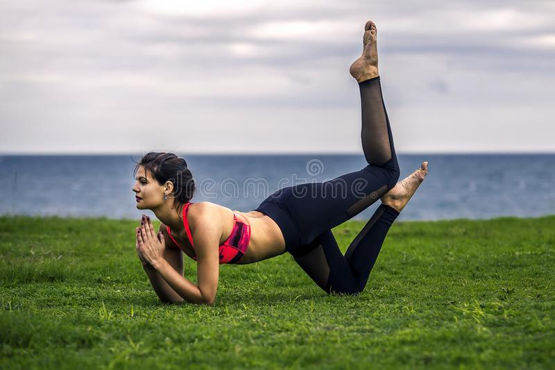 Portrait of young and sporty woman in sportswear doing yoga outside. stock photo