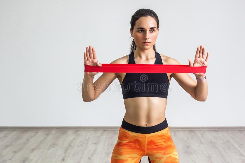 Portrait of young sporty woman wearing black top and orange leggings performs exercises for the muscles of the hands, workout with royalty free stock photos