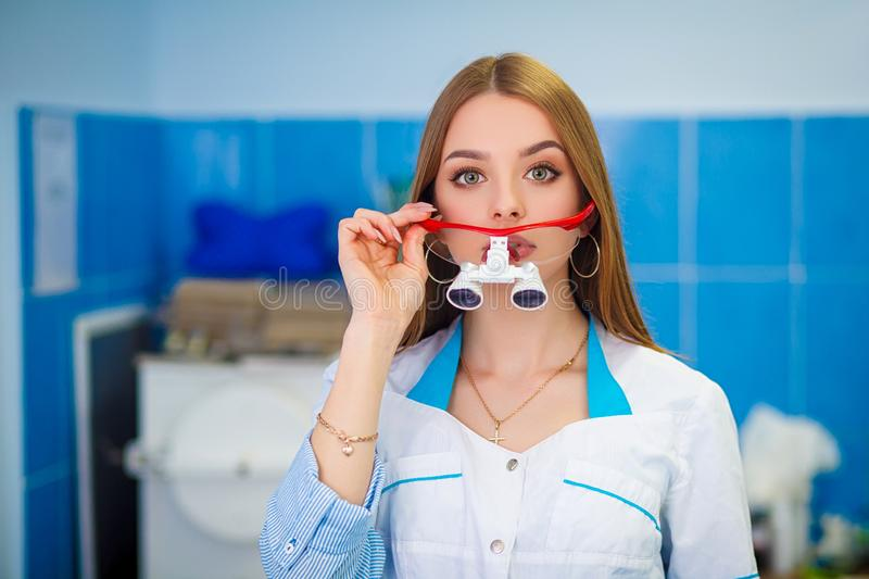 Portrait of young stomatologist making funny face while looking at camera and smiling. Health care concept. Beautiful girl in a white coat. Image of a woman royalty free stock photography