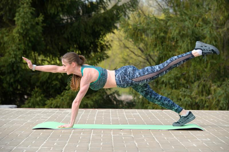 Portrait of an young strong sportswoman doing plank exercise training in green park royalty free stock images