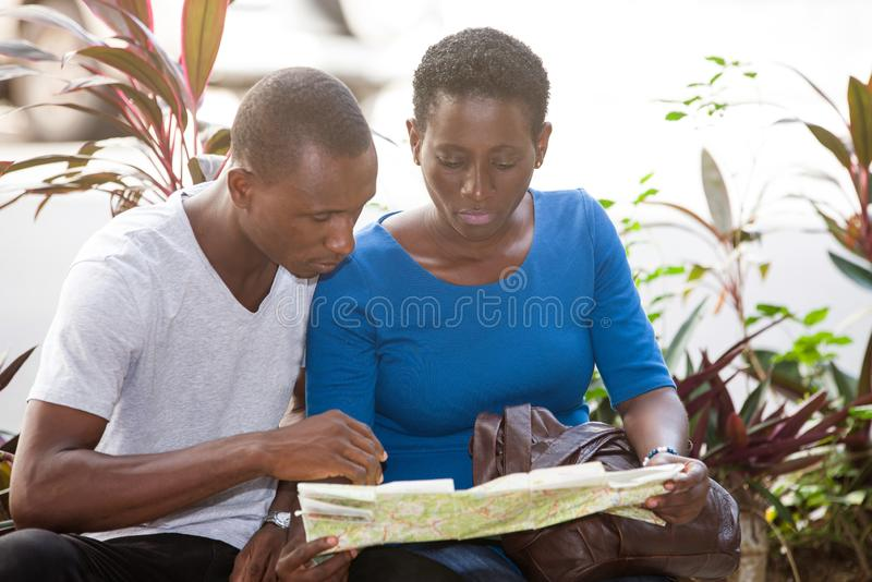 Portrait of young students sitting with map. Young students sitting in park looking at map royalty free stock image