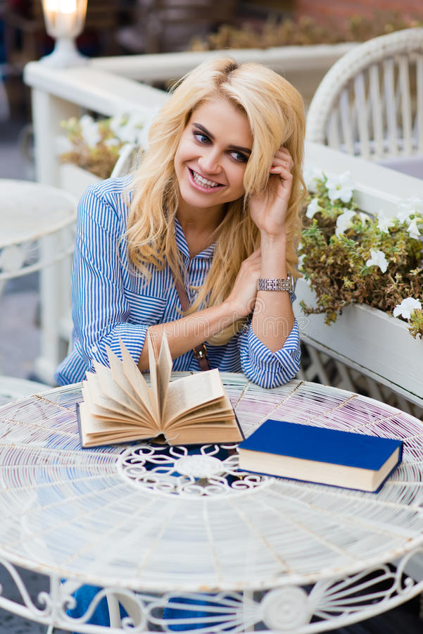Portrait of a young stunning lady with cute smile sitting with books in sidewalk cafe during her recreation time, stock photography
