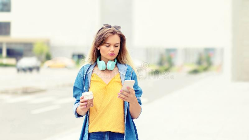 Portrait of young stylish blonde woman walking on street holding mobile phone and takeaway coffee texting on social media stock photos