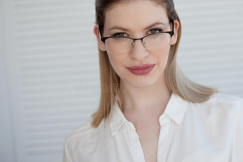 Portrait of a young stylish business woman in a white shirt and glasses. royalty free stock photo