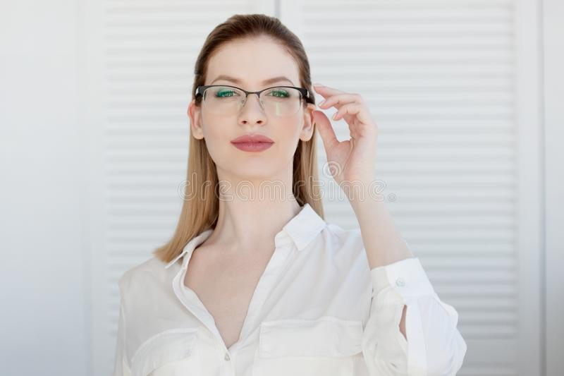 Portrait of a young stylish business woman in a white shirt and glasses. stock photography