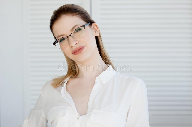 Portrait of a young stylish business woman in a white shirt and glasses. stock image