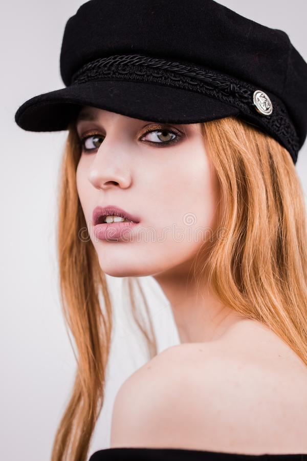 Portrait of young stylish girl model in black cap, hat with natural makeup isolated on white background. Looking at camera royalty free stock photography