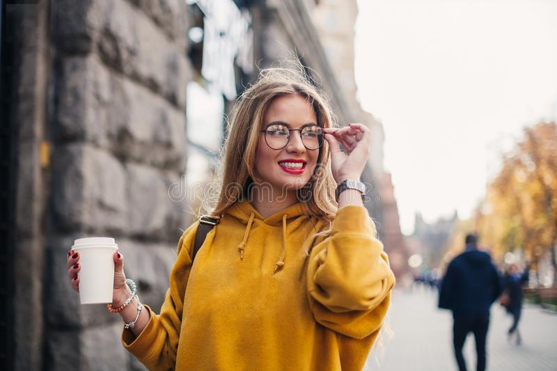 Young stylish girl student wearing bright yellow sweatshirt.Close-up portrait of inspired young woman laughing and touching glasse. Portrait young stylish girl royalty free stock photo