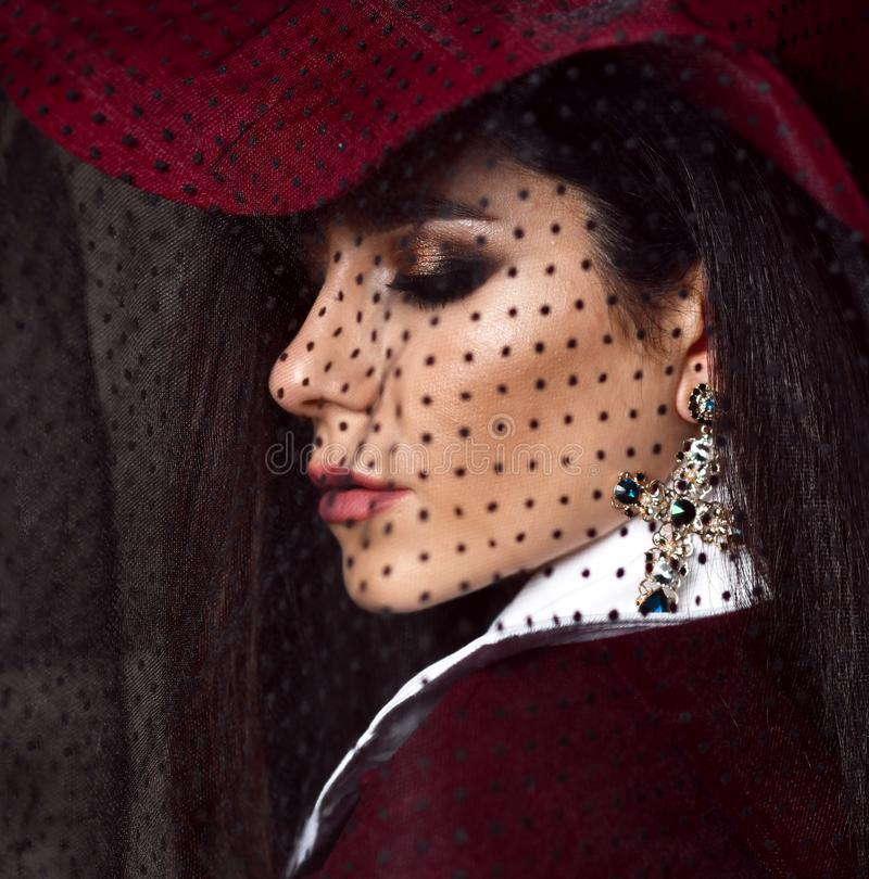 Portrait of young stylish woman brunette in dark red hat with her veil down looks over her shoulder. Portrait of young stylish high society lady brunette in dark stock photo