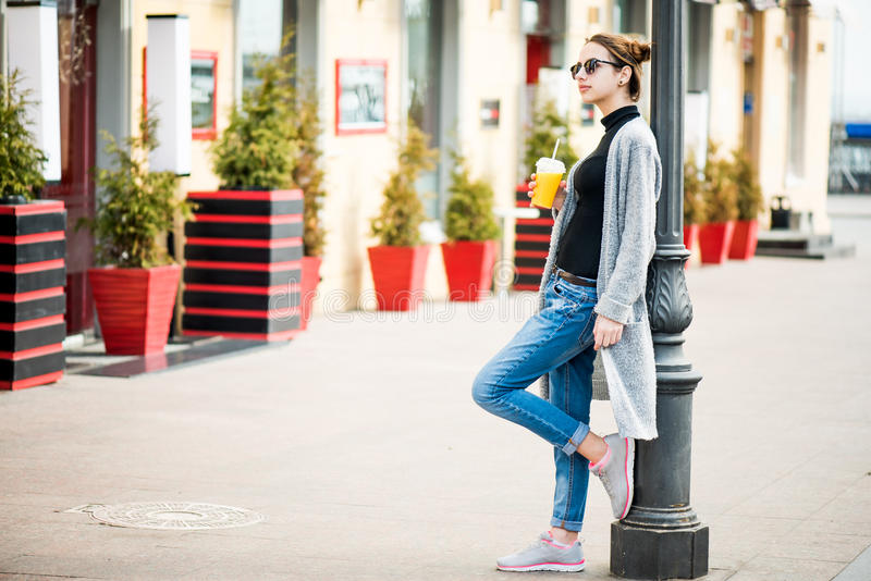 Portrait of young stylish hipster girl walking on the street. royalty free stock photos
