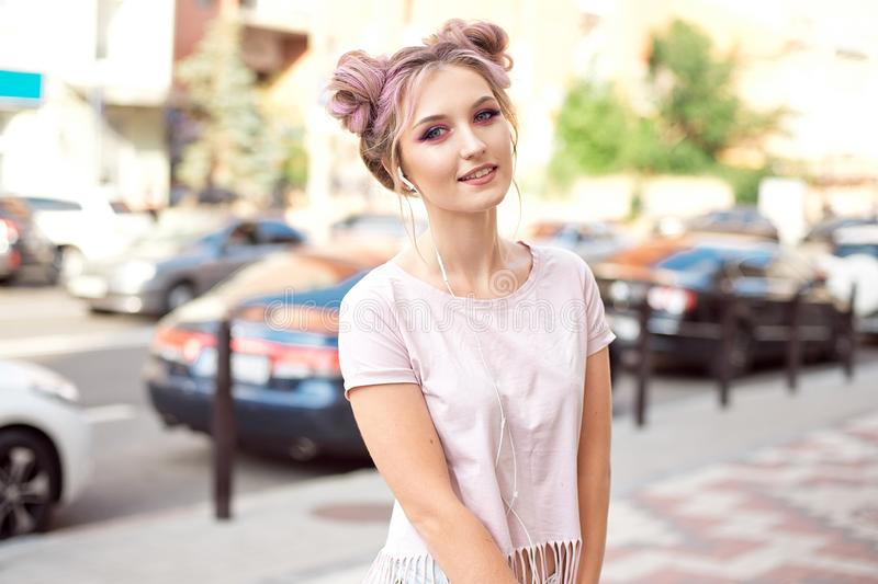 Portrait of a young stylish hipster woman walking down the street dressed in a trendy outfit, pink hairstyle bun. Traveling listening to music on headphones royalty free stock photos