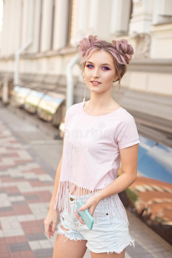 Portrait of a young stylish hipster woman walking down the street dressed in a trendy outfit, pink hairstyle bun. Traveling listening to music on headphones stock photography