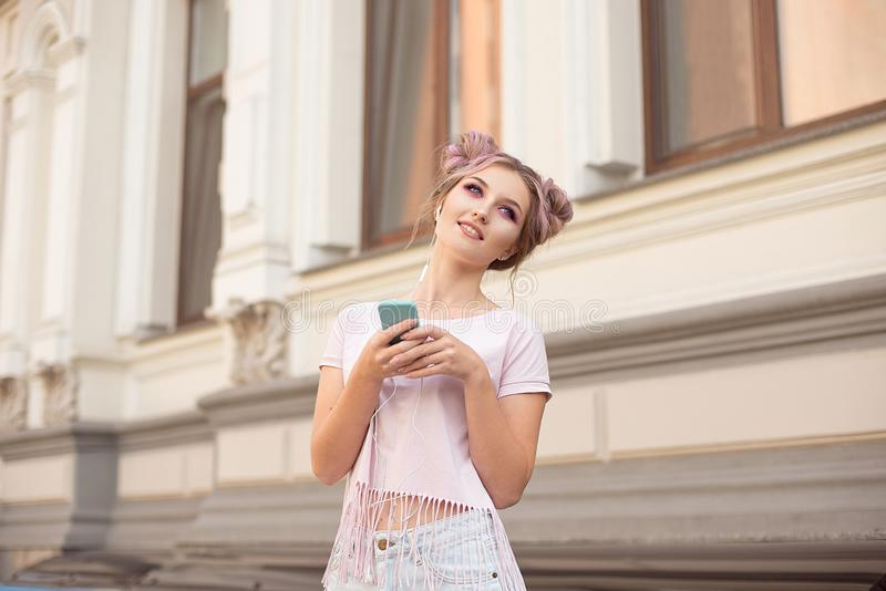 Portrait of a young stylish hipster woman walking down the street dressed in a trendy outfit, pink hairstyle bun. Traveling listening to music on headphones stock images