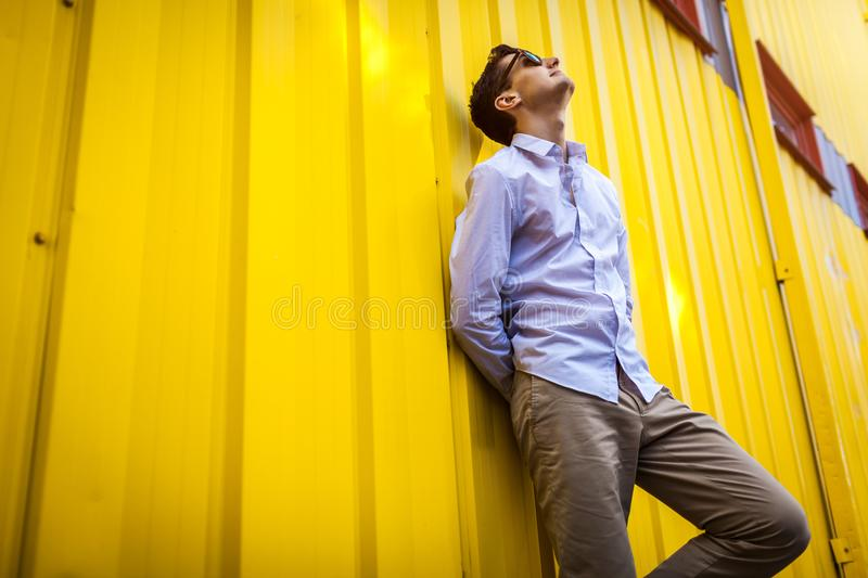 Portrait of young stylish man standing against yellow wall outdoors. Summer fashionable outfit. royalty free stock images