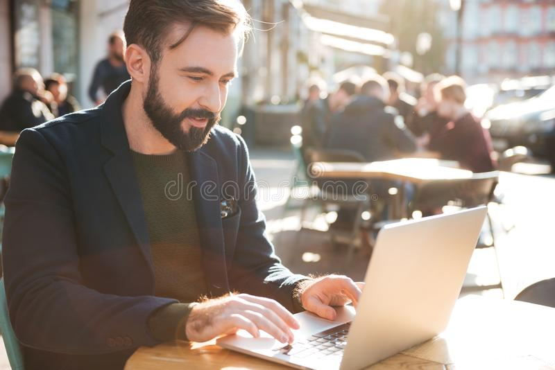Portrait of a young stylish man working on laptop computer stock photo