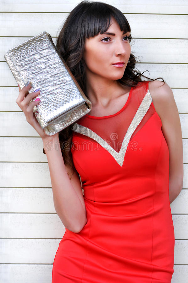 Portrait of young stylish woman in red elegant dress, holding handbag, standing in front white background, fashion shot. royalty free stock photography