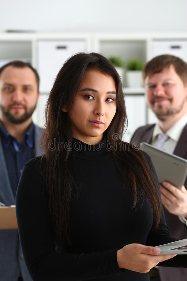 Portrait of young successful businesslady hold laptop and two businessmen in office royalty free stock photography