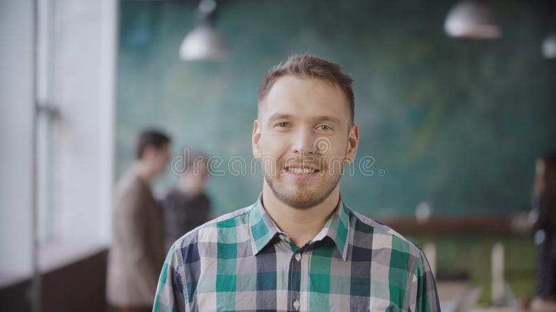 Portrait of young successful businessman at busy office. Handsome male employee looking at camera and smiling. stock images