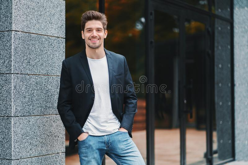 Portrait of young successful confident businessman in the city on office building background. Man in business suit royalty free stock image