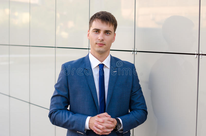 Portrait of a young successful man economist standing in modern office interior, confident male dressed in luxury corporate clothe stock photography