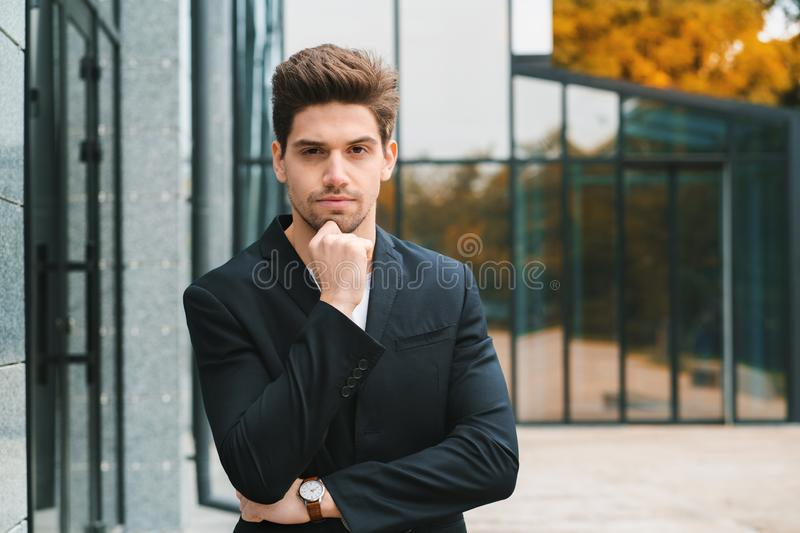 Portrait of young successful pensive businessman in city. Man in business jacket on office building background. Handsome royalty free stock images