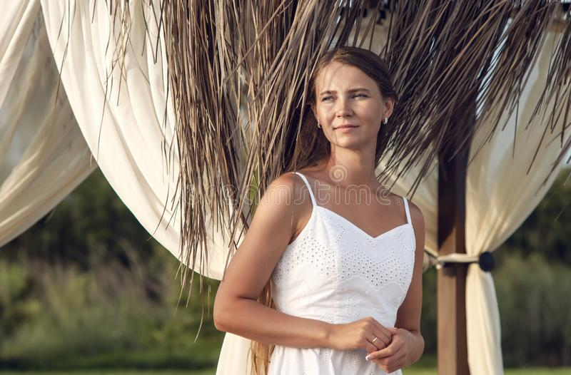Portrait young suntanned woman. In white dress royalty free stock photography