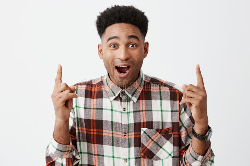 Portrait of young surprised handsome black-skinned man with afro hairstyle in casual long-sleeve shirt pointing upside stock images