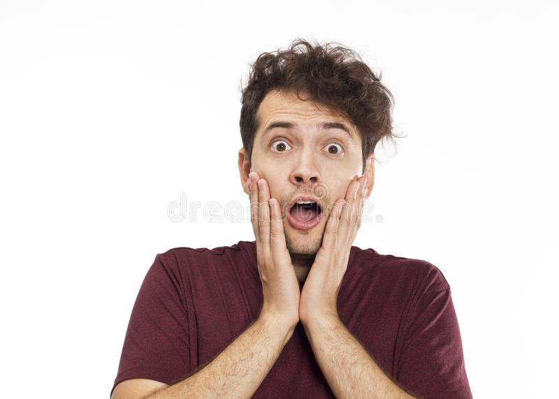 Portrait of young surprised man with opened mouth. Isolated on w stock image