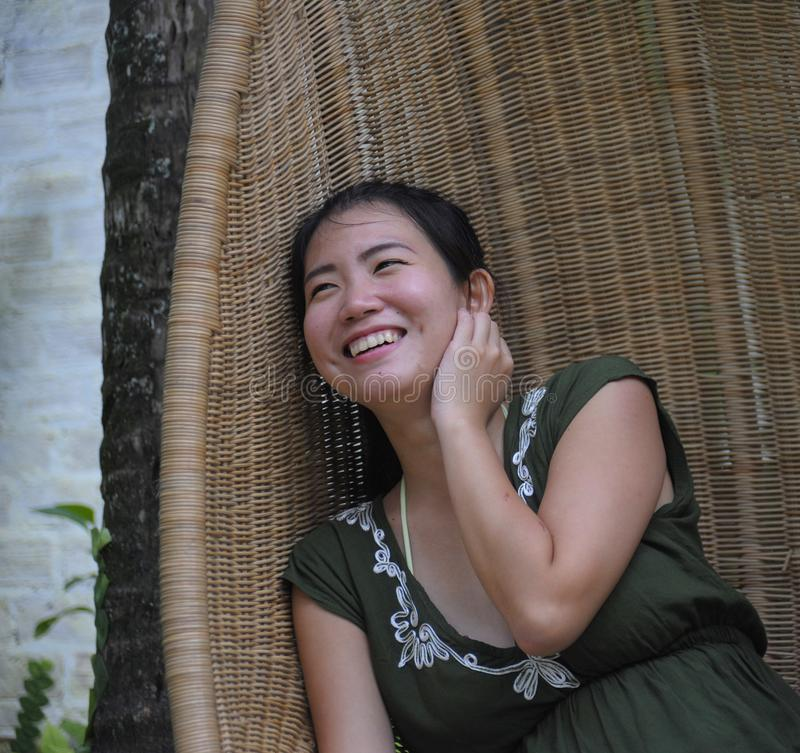 Sweet and relaxed Asian Chinese woman on her 20s wearing green Summer dress smiling happy and playful sitting at bamboo swing chai. Portrait of young sweet and stock photography