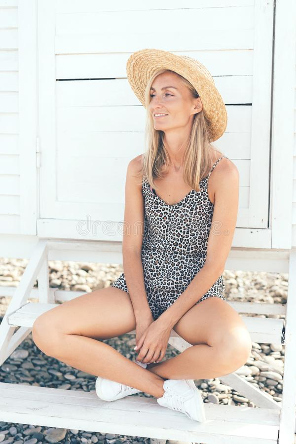 Portrait of a young tanned woman in a summer leopard print overalls stock photos