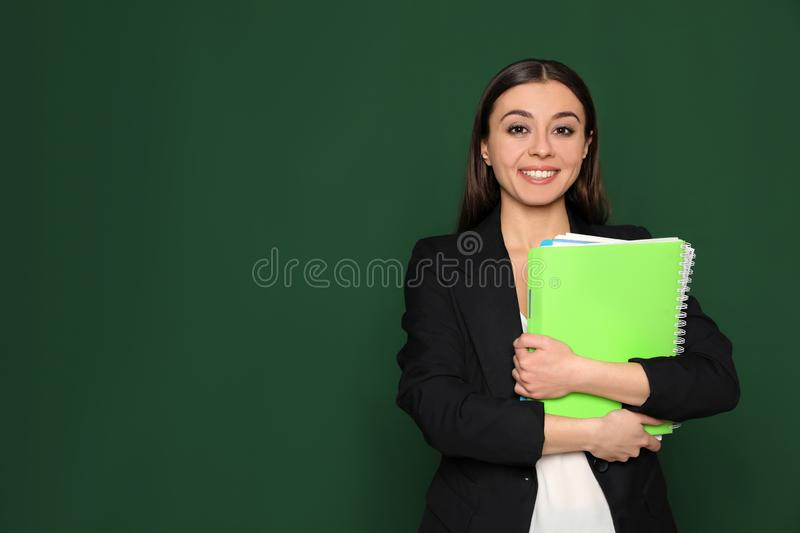 Portrait of young teacher with notebooks on green background. Space stock images