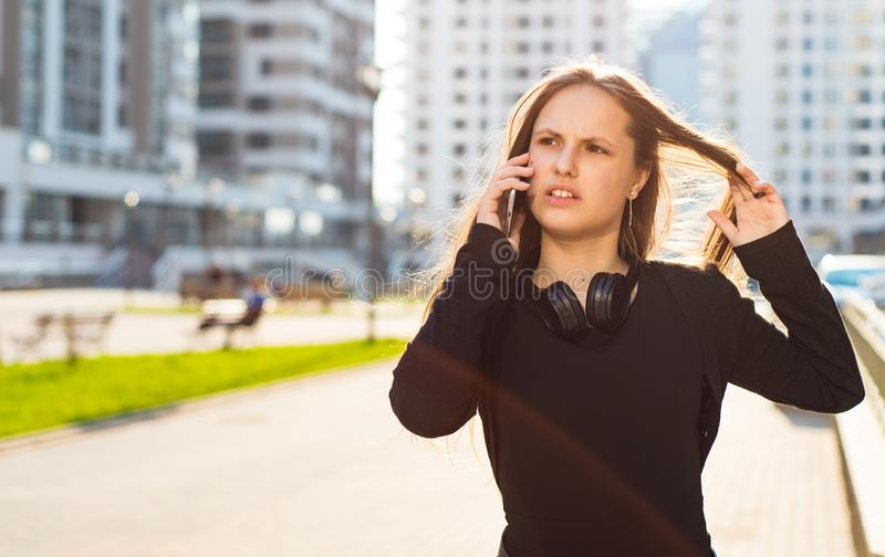 Portrait of young teenager brunette girl with long hair. girl on city in black dress talking on the smart phone in the street in a royalty free stock photos