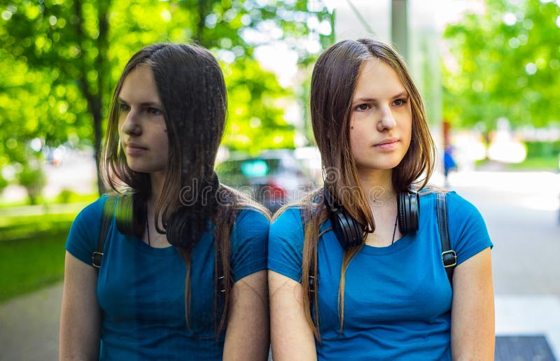 Portrait of young teenager brunette girl with long hair. an urban environment of a street warehouse, woman and reflection in the g. Outdoor portrait of young royalty free stock photo