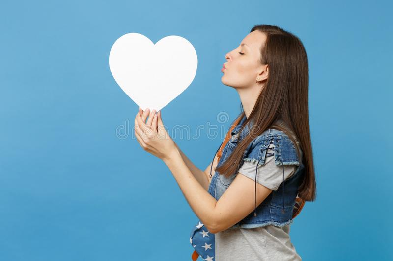 Portrait of young tender beautiful woman student with backpack sending air kiss to white heart with copy space in hand royalty free stock images