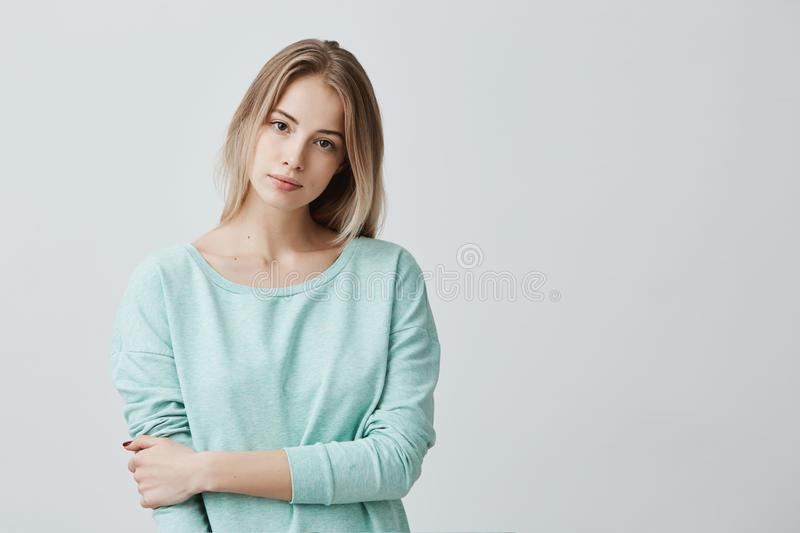 Portrait of young tender blonde european woman with healthy skin wearing light blue long-sleeved looking at camera with royalty free stock photo