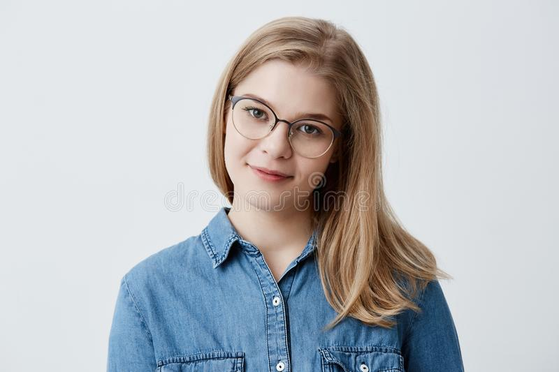 Tender blonde teenage girl with healthy skin wearing denim shirt and spectackles looking at camera with pleased or royalty free stock photo