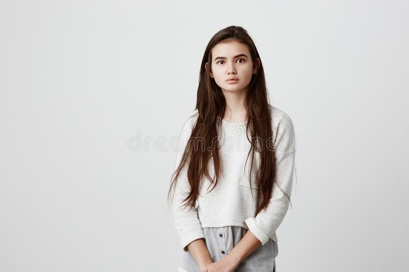 Portrait of young tender brunette girl with long dark hair and healthy skin wearing loose casual clothes looking at. Camera with calm or pleasant expression royalty free stock photography