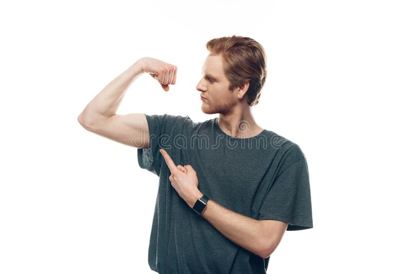 Portrait of Young Thin Man Showing Biceps. Handsome Gorgeous Guy Showing Biceps and Pointing Finger. Doing active healthy lifestyle. Isolated on White stock photos