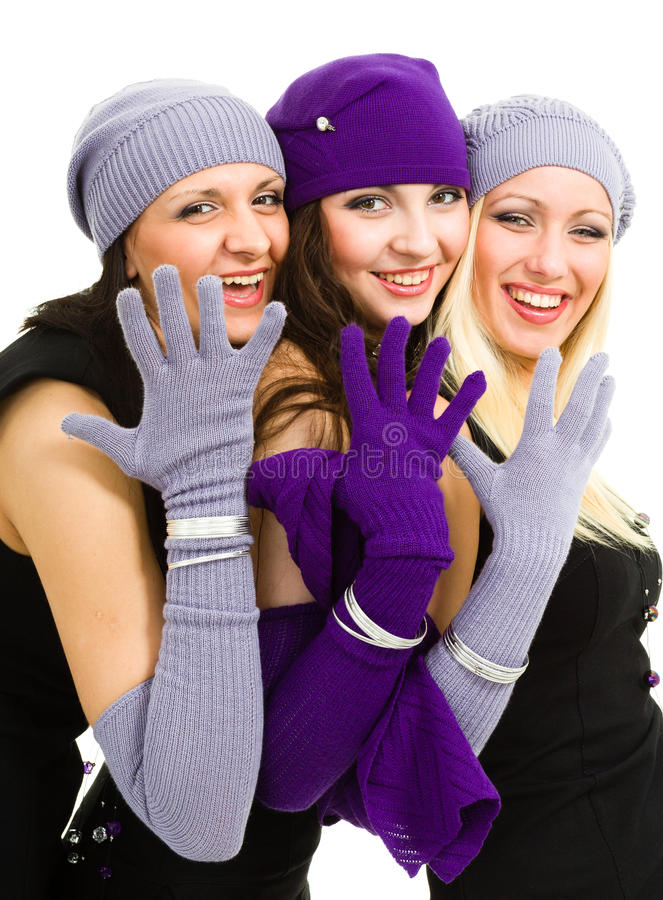 Three women in white knit wool hat and mittens. Portrait of a young three women in white knit wool hat and mittens. Isolated on white background stock photography