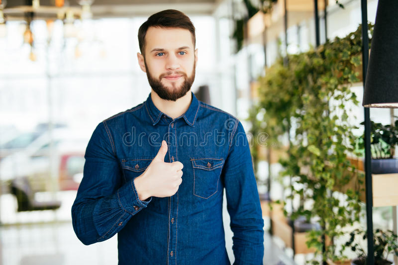 Portrait of young toothy man showing thumbs up in modern office or cafe stock photography