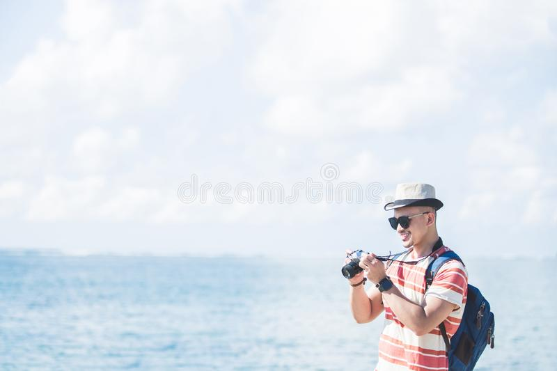 Young traveller taking photo using vintage camera. Portrait of young traveller wearing sunglasses and summer hat taking photo using vintage camera on sunny day stock images